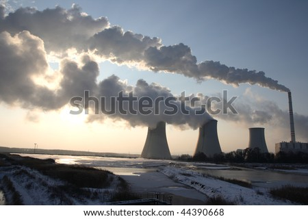 View of coal power plant against sun with several chimneys and huge fumes