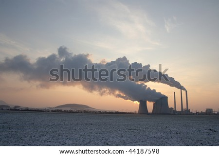 View of coal power plant during sunrise with several chimneys producing fumes