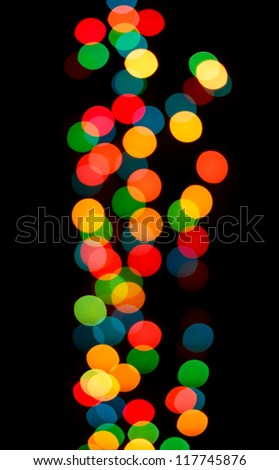 View of colorful blurry Christmas lights against black background.