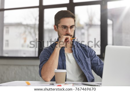 View of concentrated talented skilled male focused on screen of laptop computer, reads necessary information for creating budget report, drinks hot beverage. Attractive male freelancer keyboards text #767469670