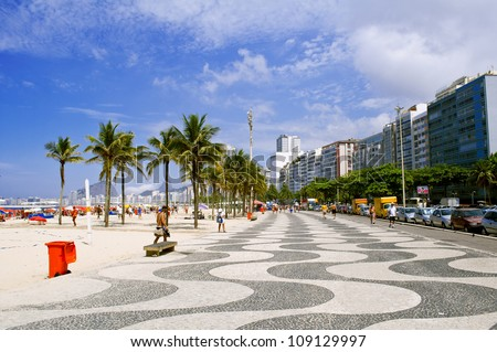 View of Copacabana beach with palms and mosaic of sidewalk