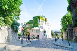 View of cosy street in quarter Montmartre in Paris, France. Cozy cityscape of Paris at summer. Architecture and landmarks of Paris.