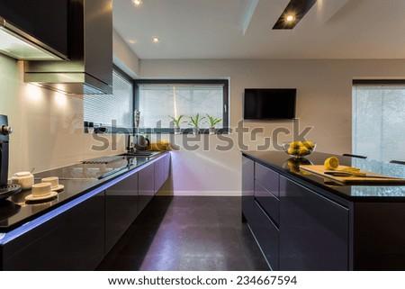 View of dark furniture in white painted kitchen