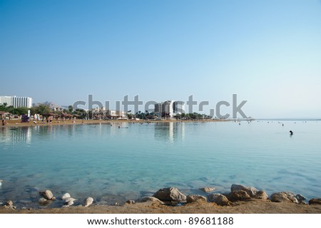 view of Dead Sea beach at Ein Bokek with salty rocks on foreground