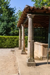 View of detail old structure with granite pillars and orange ceramic tile roof, with fountain in the interior, inserted in the Gardens of Solar de Mateus...