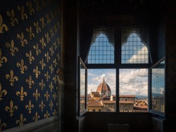 View of dome of Florence Cathedral over houses of historic centre of Florence, from a room of Palazzo Vecchio, with Fleur-de-lis pattern on wall, in Florence, Italy