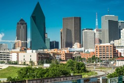 View of Downtown Dallas from the west looking east on a sunny clear day with a blue sky. There is some construction going on. Green foliage in the foreground and the railroad.