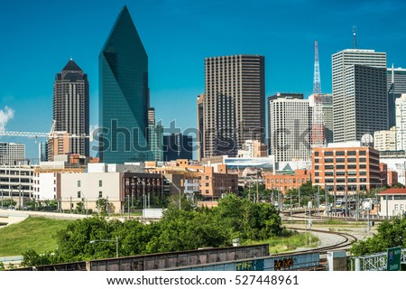 View of Downtown Dallas from the west looking east on a sunny clear day with a blue sky. There is some construction going on. Green foliage in the foreground and the railroad. #527448961
