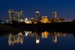 View of Downtown Fort Worth at twilight a city park with the Trinity River reflecting the skyline