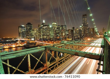 View of downtown Manhattan from the Brooklyn Bridge with traffic flying by.