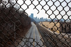View of Downtown Pittsburgh, PA through hole in chainlink fence over busway.