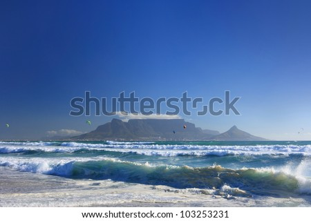 View of dramatic Table Mountain across Table Bay with big blue sky and shoreline waves in foreground.