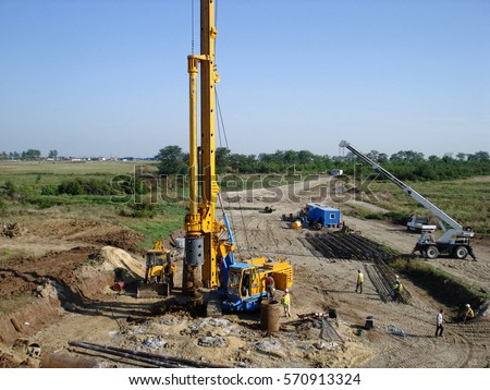 View of drilling machine, backhoe and crane