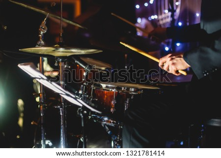 View of drum set kit on a stage during jazz rock show performance, with band performing in the background, drummer point of view   #1321781414