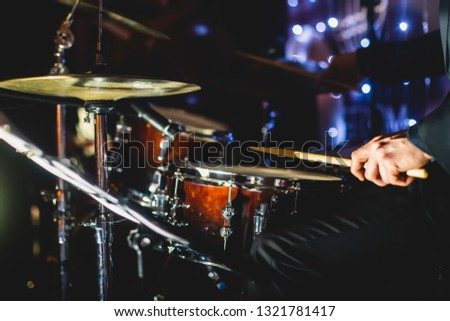 View of drum set kit on a stage during jazz rock show performance, with band performing in the background, drummer point of view   #1321781417