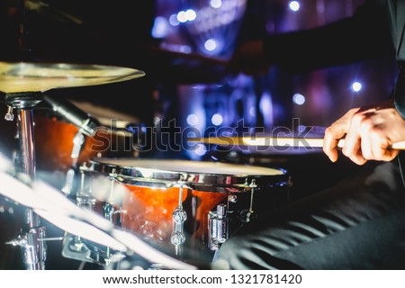 View of drum set kit on a stage during jazz rock show performance, with band performing in the background, drummer point of view   #1321781420