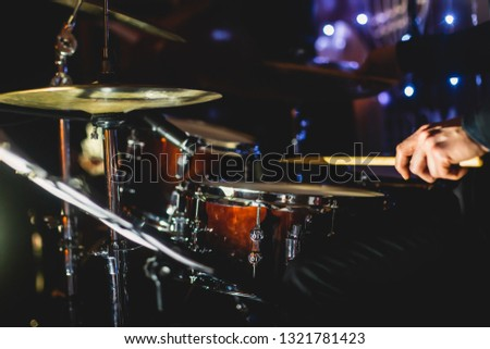 View of drum set kit on a stage during jazz rock show performance, with band performing in the background, drummer point of view   #1321781423