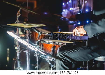View of drum set kit on a stage during jazz rock show performance, with band performing in the background, drummer point of view   #1321781426