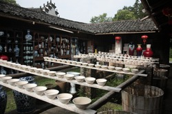 View of Drying Porcelain bowls clay body on row of wooden boards at Ancient ceramic Kiln in Jingdezhen, Jiangxi, China.