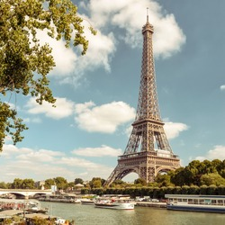 View of Eiffel tower on the river Seine, Paris, France. Old Eiffel Tour is one of the main tourist attractions in the world. Scenery of the city with the majestic construction by Eiffel in summer.