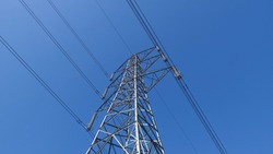 View of electricity pylon against deep blue sky with copy space