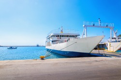 View of empty ferry in typical Greek blue white colors waiting in harbour to be loaded with cars