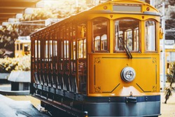 View of empty yellow glossy excursion tram waiting at tramway station in Rio de Janeiro: single headlight, opened interior with wooden windows and seats inside, shallow depth of field, sunny day