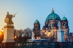 View of Evangelical Cathedral located on the Museum Island in Berlin, Germany. View of the bridge with statues at sunset. Clear sky