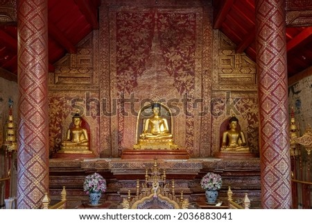 View of famous historical Phra Singh Buddha statue with beautiful ancient red and gold stencil background decor inside Viharn Lai Kham at landmark Wat Phra Singh buddhist temple, Chiang Mai, Thailand