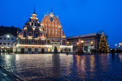 View of  famous House of the Black Heads illuminated at night and Christmas tree in Riga, Latvia. Night view of Riga Town Hall Square and Roland's Statue with Christmas decoration.