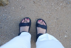 View of female feet Red nail polish Wear black shoes, and white pants Standing on the sand next to the rocks