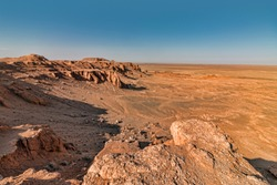 View of Flaming Cliffs in Mongolian Gobi Desert. Panoramic View of Cliffs and Surrounded Arid Plains.