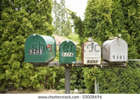 View of four rural mailboxes attached to a platform, with a fence and trees in the background. Horizontal shot.