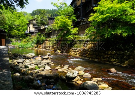 View of fresh river stream, stone bank and natural rock beach with green trees and local buildings in Kurokawa onsen town, Japan #1006945285