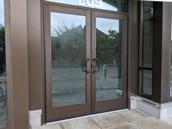 View of front doors for a business still under construction and locked with a padlock key in a shopping complex