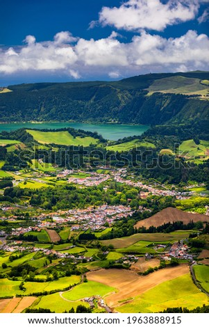 View of Furnas town and lake (Lagoa das Furnas) on Sao Miguel Island, Azores, Portugal from the Miradouro do Salto do Cavalo viewpoint. A tranquil scene of lush foliage and town in a volcanic crater Foto stock ©