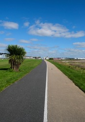 View of Galway city, Ireland from the walking & bicycle path to Salthill showing buildings, a grassy sports field and blue sky with clouds.