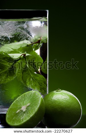 View of glass filled with green tea and some limes nearby