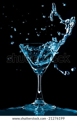 View of glass with Blue Curacao splash on black background