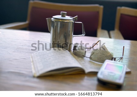View of glasses, coffee pot, a book, and a cell phone