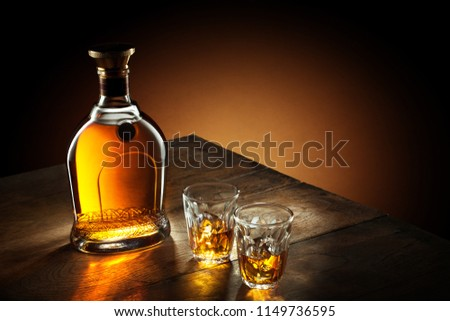view of glasses of  bourbon  and a bottle aside on color background #1149736595