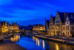View of Graslei, Korenlei quays and Leie river in the historic city center in Ghent (Gent), Belgium. Architecture and landmark of Ghent. Night cityscape of Ghent.