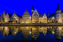 View of Graslei quay and Leie river in the historic city center in Ghent (Gent), Belgium. Architecture and landmark of Ghent. Night cityscape of Ghent.