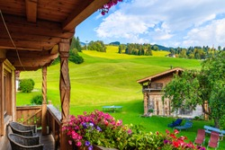 View of green meadow in mountains from typical wooden house balcony in Kirchberg village on summer day, Kitzbuhel Alps, Austria