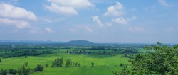 View of green rice fields and mountains under blue sky with white clouds at Kanchanaburi province, Thailand.