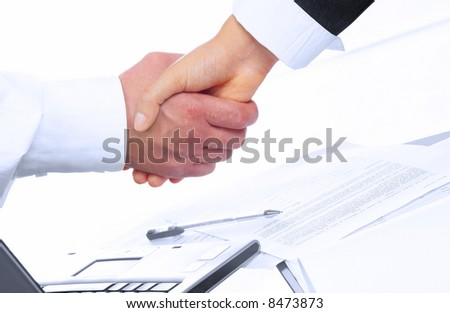 view of handshake over paper and computer in the background