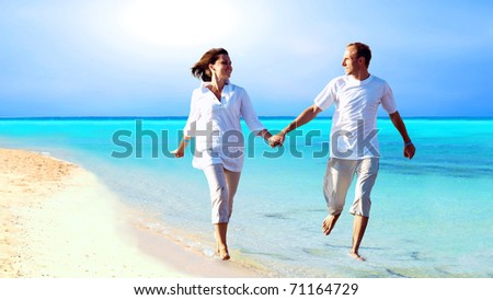 View of happy young couple walking on the beach, holding hands.