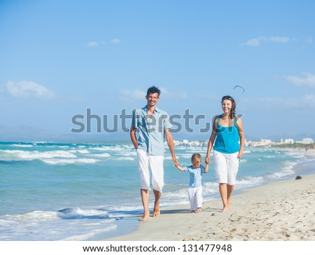 View of happy young family - mother, father and son having fun on the beach