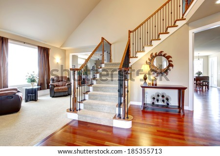 View of hardwood hallway with staircase and  living room with leather armchairs and table