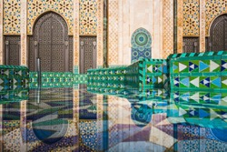 view of Hassan II mosque's big gate reflected on fountain water - Casablanca - Morocco